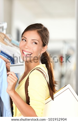 Shopping woman showing credit card smiling happy indoor in clothing shop. Young beautiful multi-ethnic Caucasian / Chinese Asian woman shopper.