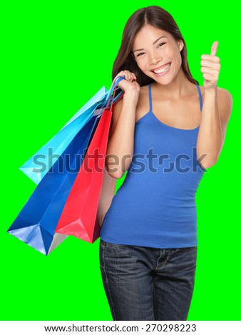 Shopping woman showing thumbs up success holding shopping bags isolated on green background. Beautiful young mixed race Asian Caucasian female shopper.