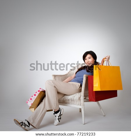Shopping woman sitting on chair and holding bags, full length portrait isolated on gray studio background.