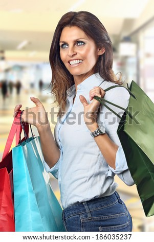 Shopping woman smiles  at department store with colorful bags in hands