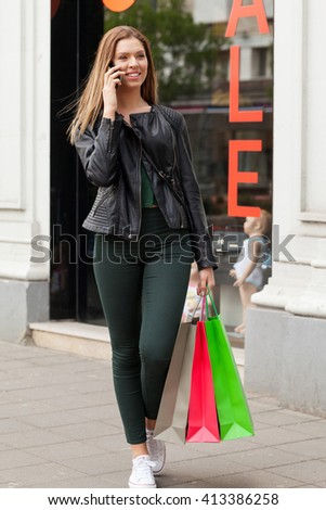Shopping woman talking on the phone while holding bags and walking at the mall  - stock photo