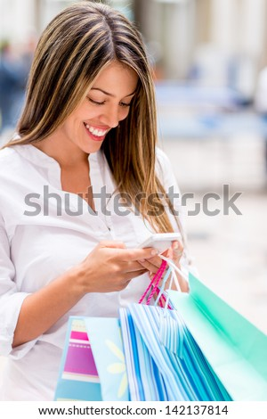 Shopping woman texting from her cell phone - stock photo