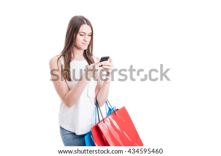 Shopping woman texting on her mobile phone and holding bags with buyings isolated on white with copyspace - stock photo