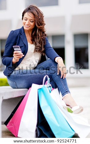 Shopping woman texting on her mobile phone with bags - outdoors - stock photo