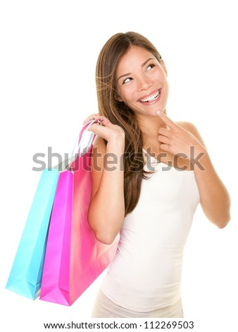 Shopping woman thinking looking up at copy smiling fresh and happy. Beautiful young multiracial Asian / Caucasian female shopper isolated on white background.