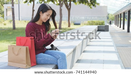 Shopping woman using cellphone at outdoor