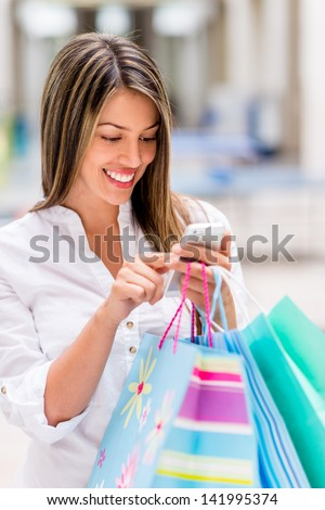 Shopping woman using smart phone at the mall - stock photo