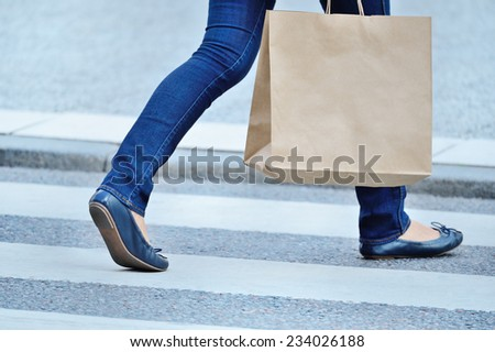 Shopping woman walking cross the street. Place for logo on bag. - stock photo