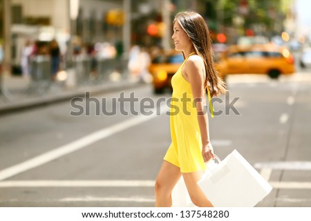Shopping woman walking outside in New York City holding shopping bags. Shopper smiling happy crossing the street outdoors while on travel on Manhattan, United States. Beautiful model in summer dress. - stock photo