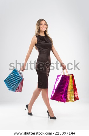 Shopping woman walking with bags isolated on white background. Happy shopping girl with colorful bags looking into camera - stock photo