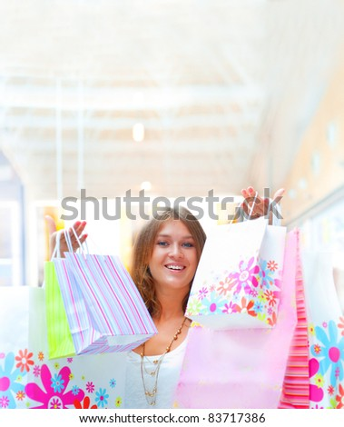 Shopping woman with lots of bags smiles inside mall. She is happy about huge christmas preseason discounts. Lots of Copyspace