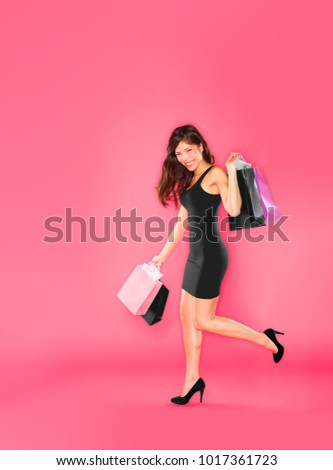 Shopping woman with shopping bag in fashion black dress and high heels outfit on pink studio background with leg up. Smiling Asian girl happy walking full length on a lot of copyspace texture.