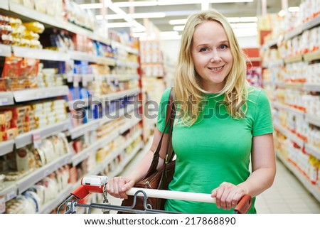 Shopping. Woman with shopping cart trolley in store or supermarket - stock photo