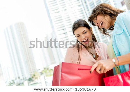 Shopping women looking at purchases in a bag and smiling