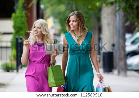 Shopping Women with Digital Tablet on street. - stock photo
