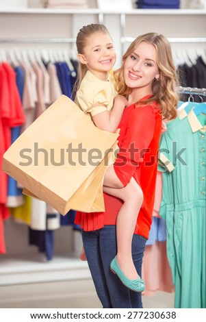 Shopping. Young mother standing in a fashion store holding her daughter with packages both smiling