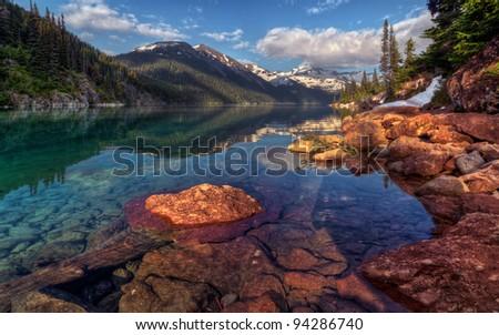 Shore bend and symmetric mountain lake reflection - stock photo