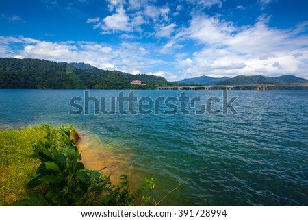 Shore of a tropical lake and islands in cloudy blue sky. Belum resort, Banding, Temenggor Lake. Malaysia