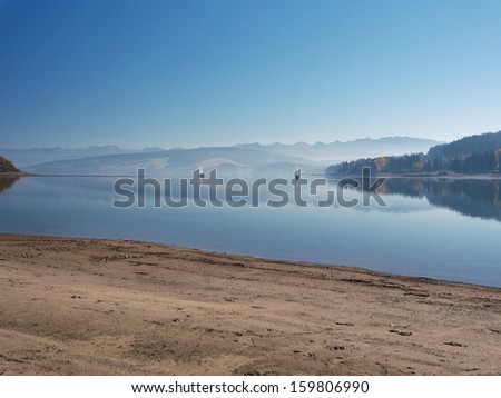 Shore of Orava reservoir early in the morning. Orava reservoir lake is located near Namestovo town in northernmost Slovakia. This location is protected by the Horna Orava Protected Landscape Area. - stock photo