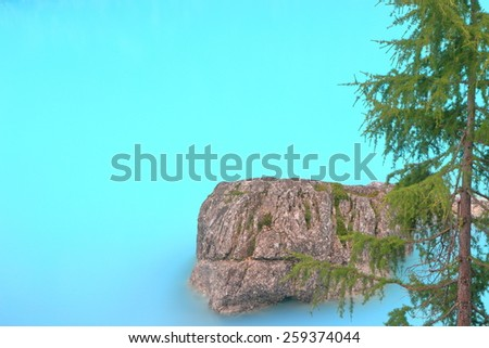 Shore of Sorapis lake with large boulder and pine tree, Dolomite Alps, Italy - stock photo