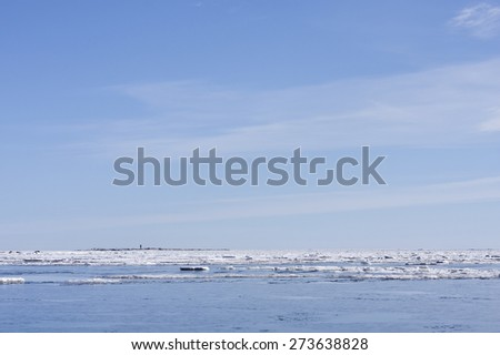 Shore of the Baltic Sea in March during the day, hours when the ice at sea breaks up. Sunny day by the sea. Lighthouse, beacon in the background. - stock photo