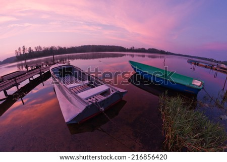 Shore of the Seliger lake (Russia) with forest  during sunrise with blue sky and red and purple clouds along with their reflections in the water surface as a background and two boats as a foreground.