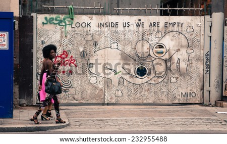 """Shoreditch, London, UK, September 28 2014: Two stylish hipster girls walking in front of a wall decorated with a graffiti with the words """"Look inside us we are empty"""" - stock photo"""