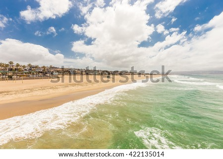 Shoreline of a Sandy Beach On a Beautiful Sumer Day with Blue Sky and Clouds. - stock photo