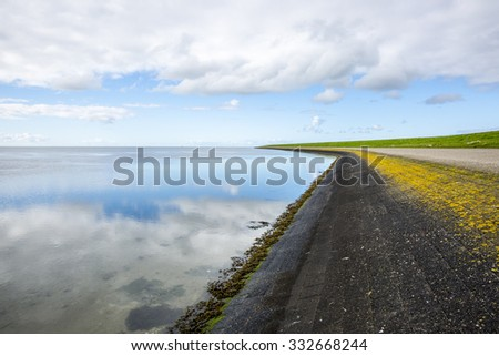 shoreline of Ameland Island, with view over the wadden sea, with clouds reflecting in water at dawn and a bike lane over a dike - stock photo