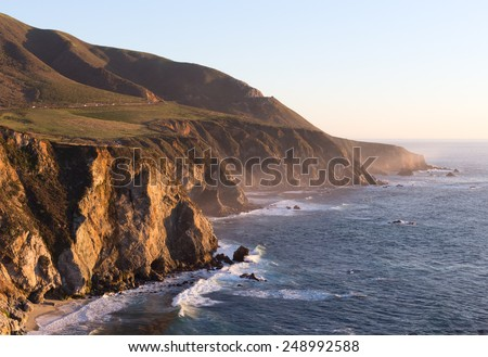 Shoreline rocks and ocean coast line newt to Big Sur California state park in sunset light with waves and stones on beach  - stock photo