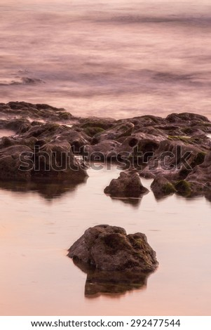 Shoreline view of the ocean water bathing the coastline. - stock photo