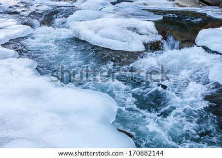 Shores of mountain river in winter time - stock photo