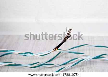 Short circuit, burnt cable, on color wooden background - stock photo
