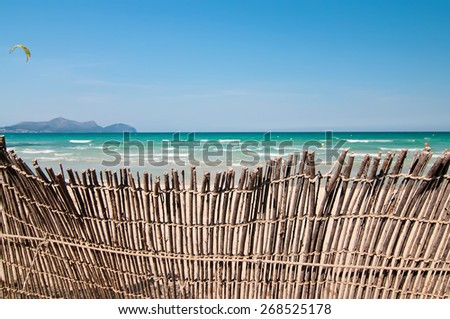 Short depth-of-field shot of a fence at the beach. Lots of sky and sunlight and space. - stock photo