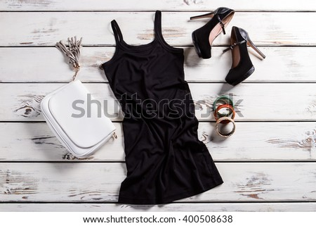 Short dress and black shoes. Glamour outfit on shop showcase. Attractive clothes for young women. Dark female outfit for parties. - stock photo