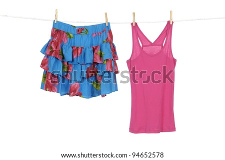 Short flower skirt and red sundress on a clothespins on rope