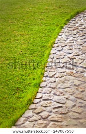Short grass lawn and cobblestone pavement texture - stock photo
