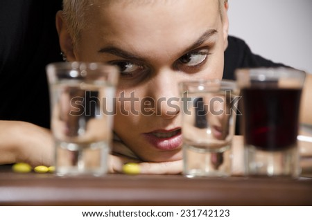 Short hair drunk young girl looking at alcohol shooters with lust. Selective focus on girl