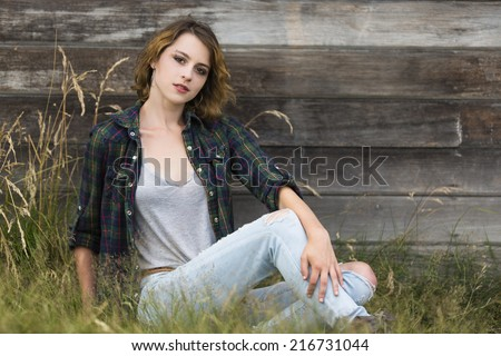 Short hair girl posing and sitting on the ground with a sassy smile - stock photo