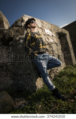 short haired brunette girl wearing a sweatshirt is standing  leaning on an old building - stock photo