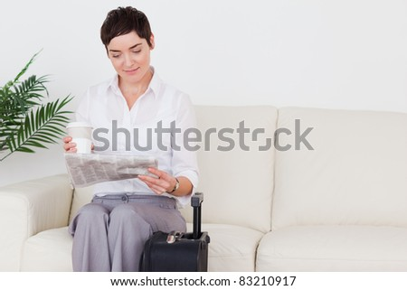 Short-haired charming woman with a suitcase, a newspaper and a cup in a waiting room
