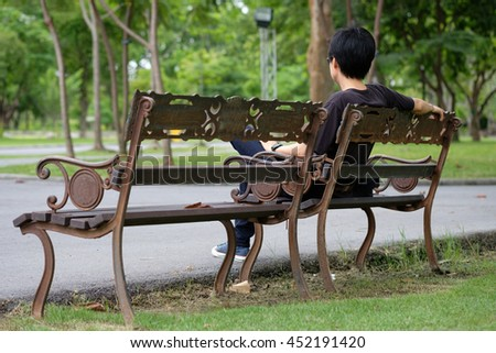 Short- haired woman sitting alone in a garden .
