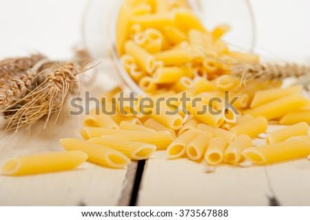 short Italian pasta penne with durum wheat grains - stock photo