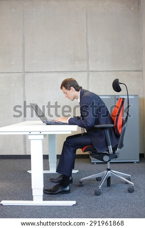 short-sighted business man bad sitting posture at laptop . - stock photo