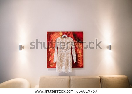 Short white dress hangs on red picture on the wall