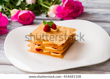 Shortcake with raspberries. Custard and mint leaves. Millefeuille with berries. Expensive dessert in local restaurant. - stock photo