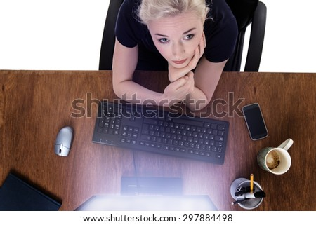 shot from above of a woman working at her desk with the computer screen glowing  - stock photo