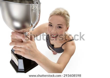 Shot from above of woman holding a large trophy looking happy and excited - stock photo
