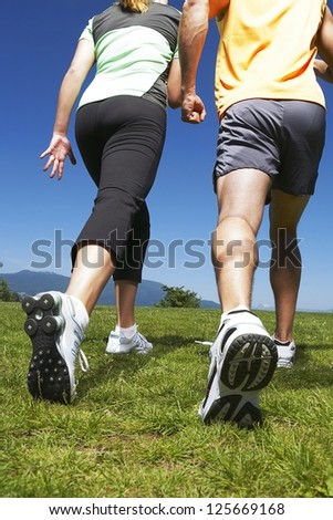 shot from below of a couple walking on a grass field wearing sneakers, exercise outfit, blue sky visible in the background