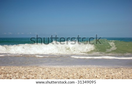 Shot from ground level the image shows the crashing of a wave and the swell right before it breaks. - stock photo